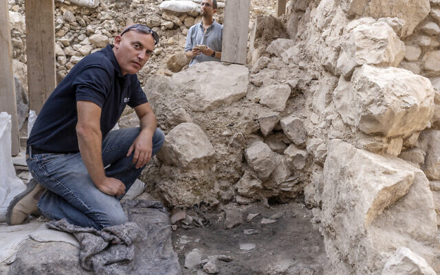 Dr. Yiftah Shalev next to the smashed First Temple pottery vessels that were found at the site with remnants of the 586 BCE destruction of Jerusalem by the Babylonians at excavations in the City of David Park in Jerusalem.(Shai Halevi/Israel Antiquities Authority)