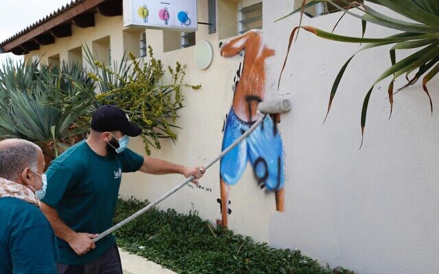 Tel Aviv Municipality workers remove a mural of boys peeping into the women's changing room at Metzitzim beach in Tel Aviv, August 23, 2020. (Ron Huldai/ Twitter)