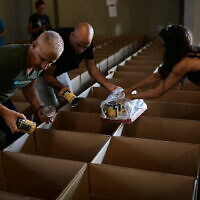 Israelis pack food packages for the needy ahead of Rosh Hashana, on September 25, 2019, in Tel Aviv. (Tomer Neuberg/Flash90)