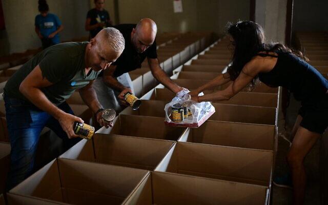 Israelis pack food packages for the needy ahead of Rosh Hashana, on September 25, 2019, in Tel Aviv. (Tomer Neuberg/Flash90)