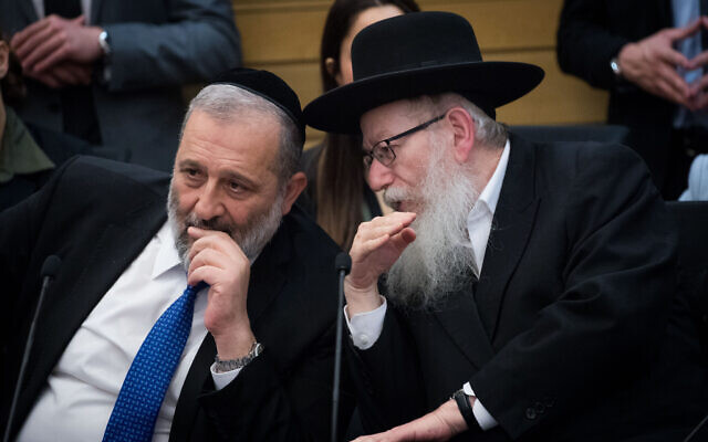 Shas party chairman and Interior Affairs Minister, Aryeh Deri, left, speaks with United Torah Judaism party leader, then health minister, Yaakov Litzman in the Knesset, March 4, 2020. (Yonatan Sindel/ Flash90)