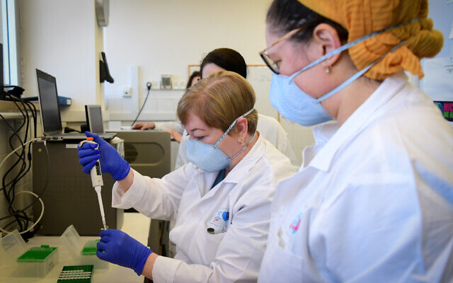 Medical workers at the Barzilay Hospital, in Ashkelon handle a coronavirus test sample on March 29, 2020 (Flash90)