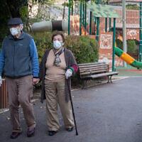 An elderly couple walk in a public park in the Rehavia neighborhood of Jerusalem, April 13, 2020. (Yonatan Sindel/Flash90)