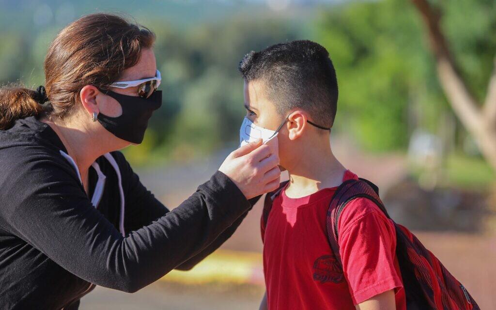 Israeli children wear face masks on their way to school in Moshav Yashresh, on May 3, 2020. (Yossi Aloni/Flash90)