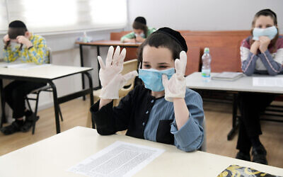 Ultra-Orthodox students from the Bnei Moshe Kretchnif school wearing face masks at their school in the city of Rehovot, on May 24, 2020. (Yossi Zeliger/Flash90)