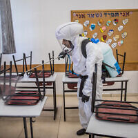 Workers disinfect a classroom at the Gymnasia Rehavia high school in Jerusalem on June 3, 2020. (Yonatan Sindel/Flash90)