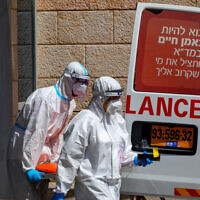 Magen David Adom workers wearing protective clothing seen after evacuating a man with suspicion for coronavirus at Hadassah Ein Karem Medical Center in Jerusalem, on July 20, 2020 (Olivier Fitoussi/Flash90)