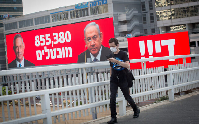 A man wearing a protective mask walks by a sign stating the number of unemployed in Israel, alongside the word 'Enough!!' in Tel Aviv, on July 22, 2020 (Miriam Alster/Flash90)