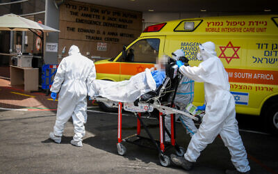 Illustrative: Magen David Adom workers wearing protective clothing move a patient outside the coronavirus unit at the Sheba Medical Center in Ramat Gan on July 27, 2020. (Yossi Zeliger/Flash90)