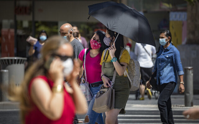 Jerusalem residents, wearing face masks for fear of the coronavirus, walk on Jaffa road in the city center of Jerusalem, August 2, 2020. (Olivier Fitoussi/Flash90)