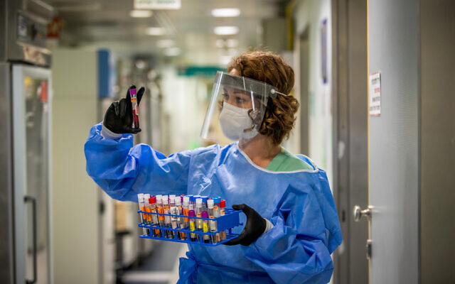 A technician carries out a diagnostic test for coronavirus in a lab at the Ichilov Hospital in Tel Aviv, on August 3, 2020. (Yossi Aloni/Flash90)