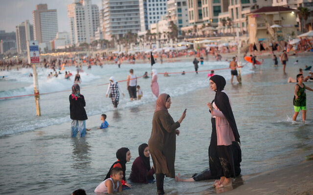 Arab women enjoy the beach in Tel Aviv on August 4, 2020. (Miriam Alster/Flash90)