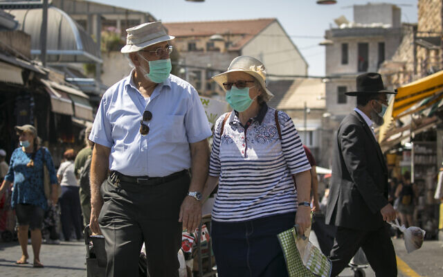 Israelis, wearing face masks for fear of the coronavirus, shop at the Mahane Yehuda market in Jerusalem on August 4, 2020. (Olivier Fitoussi/Flash90)