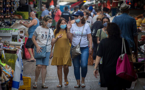 Israelis wear protective face masks as they shop for food at the Carmel market in Tel Aviv on August 5, 2020. (Miriam Alster/FLASh90)