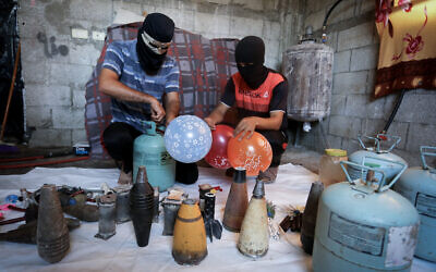 Palestinians in the southern Gaza city of Rafah prepare balloon-borne incendiary devices to be launched toward Israel on August 8, 2020. (Abed Rahim Khatib/Flash90)