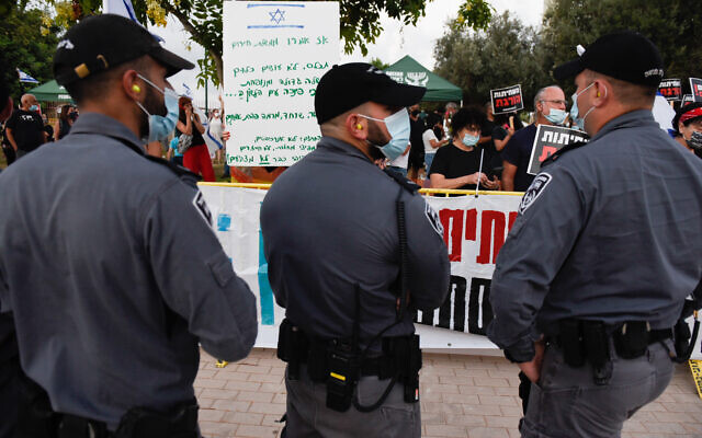 Police officers stand in front of protesters demonstrating against Prime Minister Benjamin Netanyahu near his home in the coastal town of Caesarea on August 8, 2020. (Meir Vaknin/Flash90)