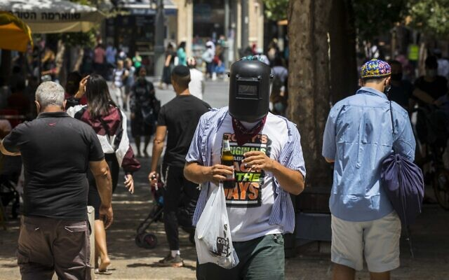 Israelis wearing face masks due to the coronavirus pandemic walk on Jaffa Street in Jerusalem on August 9, 2020. (Olivier Fitoussi/Flash90)