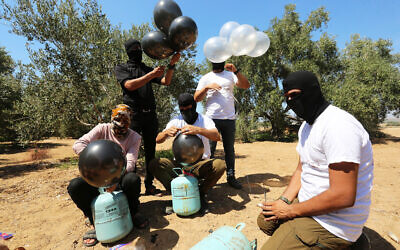Palestinians prepare a flammable object to be flown toward Israel, near the Israel-Gaza border, in the eastern part of the Gaza Strip, August 10, 2020. (Abed Rahim Khatib/Flash90)