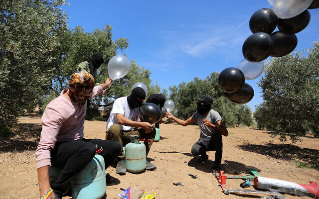 Palestinians prepare an indenciary to be flown toward Israel by balloon, near the Israel-Gaza border, in the eastern part of the Gaza Strip, August 10, 2020. (Abed Rahim Khatib/Flash90)