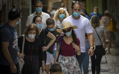 People wearing face masks due to coronavirus outbreak walk in the Old City of Jerusalem on August 10, 2020. (Olivier Fitoussi/Flash90)