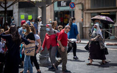 People walk with face masks on Jaffa street in Jerusalem on August 10, 2020. (Yonatan Sindel/Flash90)