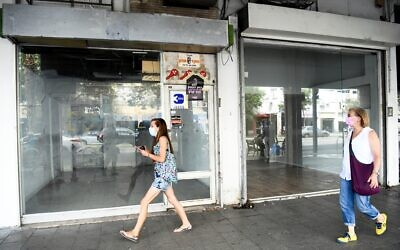 People walk next to empty shops in Tel Aviv on August 11, 2020. (Flash90)