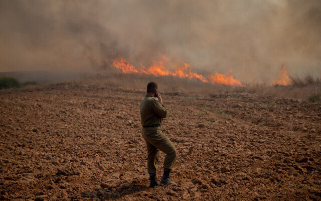 Illustrative: An IDF soldier stands in front of a fire near Kibbutz Be'eri in southern Israel that was sparked by a balloon-borne incendiary device launched from the Gaza Strip, August 13, 2020. (Yonatan Sindel/Flash90)