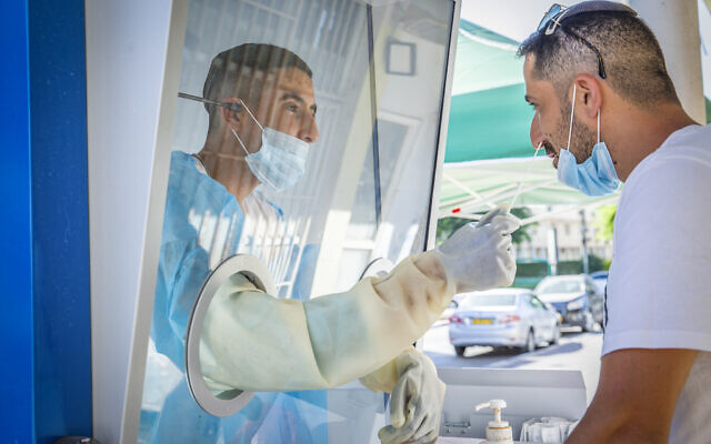 A healthcare worker takes samples from Israelis to test them for the coronavirus at a mobile testing station in the central city of Ramle, August 18, 2020. (Yossi Aloni/Flash90)
