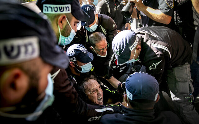 Police remove former Shin Bet head Carmi Gillon from the protest tent against Prime Minister Benjamin Netanyahu outside the PM's Residence in Jerusalem, on August 20, 2020. (Olivier Fitoussi/Flash90)