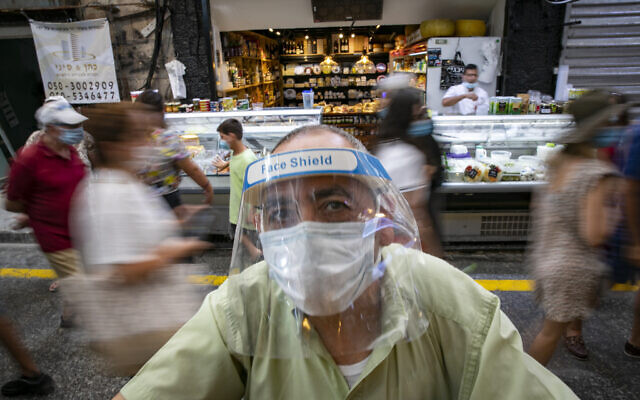 Israelis, wearing face masks for fear of the coronavirus, shop for grocery at the Mahane Yehuda market in Jerusalem on August 20, 2020. (Olivier Fitoussi/Flash90)