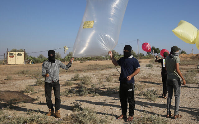 Palestinians near Rafah in the southern Gaza Strip prepare to release balloon-borne explosive and incendiary devices towards Israel on August 21, 2020. (Fadi Fahd/Flash90)
