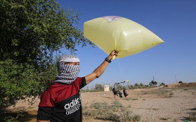 Palestinian men prepare to release balloon-borne explosive and incendiary devices toward Israel near Rafah, along the Israel-Gaza border, on August 21, 2020 (Fadi Fahd/Flash90)