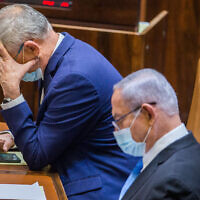 Defense Minister Benny Gantz (left) and Prime Minister Benjamin Netanyahu seen during a vote to stave off a budget deadline and thus avert elections, at the Knesset on August 24, 2020. (Oren Ben Hakoon/Pool)