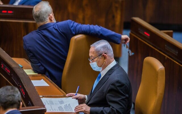 Alternate Prime Minister and Minister of Defense Benny Gantz (left) and Prime Minister Benjamin Netanyahu seen during a vote to stave off a budget deadline and thus avert elections, at the Knesset on August 24, 2020.(Oren Ben Hakoon/POOL)