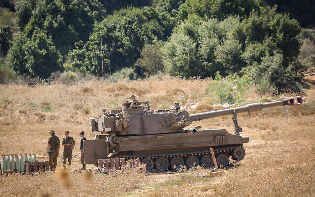 Israeli soldiers stand near artillery howitzers deployed near the Lebanese border in northern Israel on August 26, 2020. (David Cohen/Flash90)