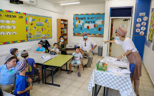 First-grade students and their parents in a classroom ahead of the opening of the school year at Orot Etzion School, in the West Bank settlement of Efrat, August 30, 2020. (Gershon Elinson/Flash90)