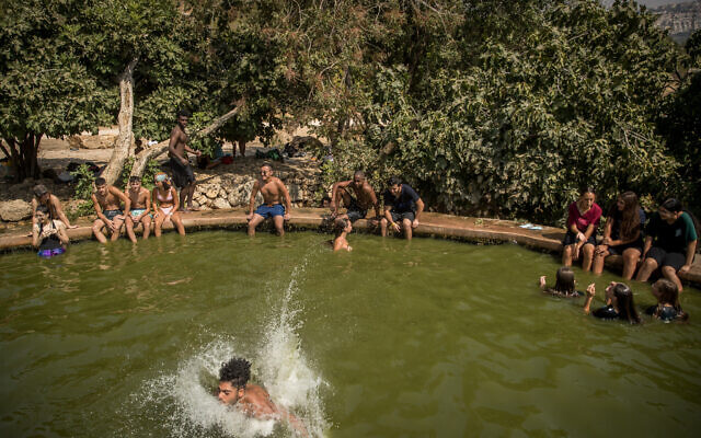 People enjoy a hot summer day at the Ein Lavan Spring in the Jerusalem Mountains on August 30, 2020. (Yonatan Sindel/Flash90)