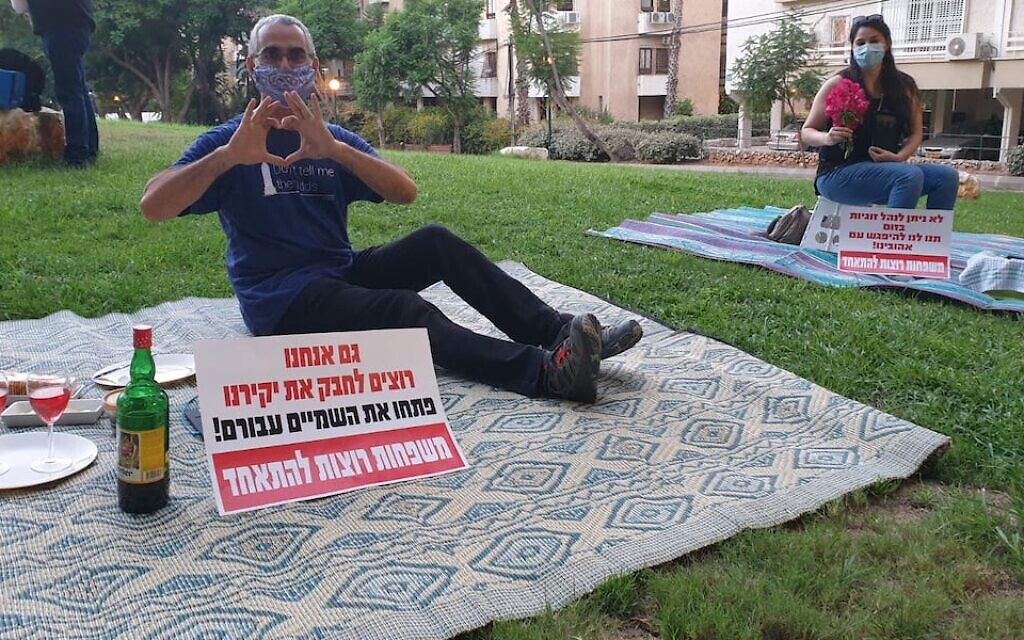 """Israelis protest being separated from their significant others outside the residence of the foreign minister by having solo romantic picnics on the eve of Tu B'Av, the Jewish day celebrating love. The signs read, """"We also want to embrace our loved ones. Open the skies for them. Families want to be together."""" (Courtesy: Plia Kettner via JTA)"""