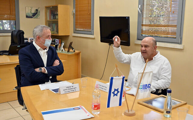 Defense Minister Benny Gantz, left, speaks with the director of the Institute of Biological Research, Prof. Shmuel Shapira, at the laboratory in Ness Ziona on August 6, 2020. (Ariel Hermoni/ Defense Ministry)