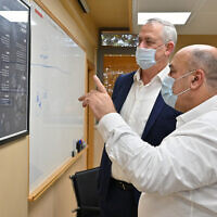 Defense Minister Benny Gantz, left, speaks with the director of the Institute of Biological Research, Prof. Shmuel Shapira, at the laboratory in Ness Ziona on August 6, 2020. (Ariel Hermoni/Defense Ministry)