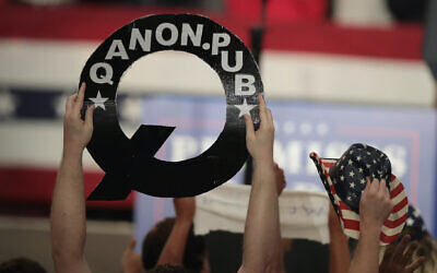 An attendee at a rally for an Ohio congressional candidate holds a QAnon sign as President Donald Trump speaks, Aug. 4, 2018. (Scott Olson/Getty Images via JTA)