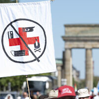 01 August 2020, Berlin: A flag on which various symbols from a Red Cross form a swastika is shown by a participant in the demonstration against corona restrictions in front of the Brandenburg Gate. (Fabian Sommer/picture alliance via Getty Images via JTA)