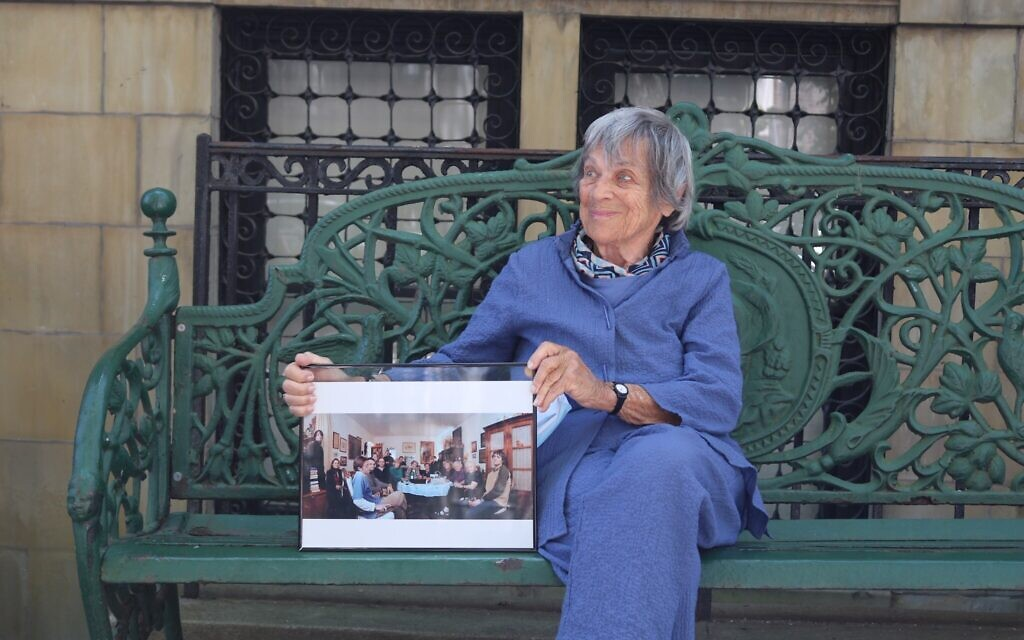 94-year-old Trudy Jeremias has taken over hosting the Stammtisch since 2015. Here, in 2020, she holds a photo of the regular Wednesday meeting at the home of her predecessor, Gaby Glueckselig. (Hannah Harnest/ Times of Israel)
