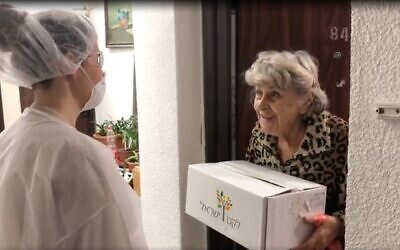 An elderly lady receives a meal delivery courtesy of Leket, the National Food Bank. (Courtesy, Leket)
