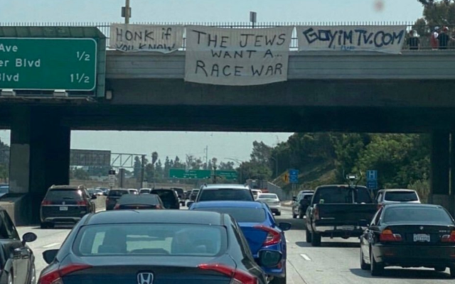 A sign reading 'The Jews want a race war' is seen on a highway overpass in Los Angeles. (Siamak Kordestani/Twitter via JTA)
