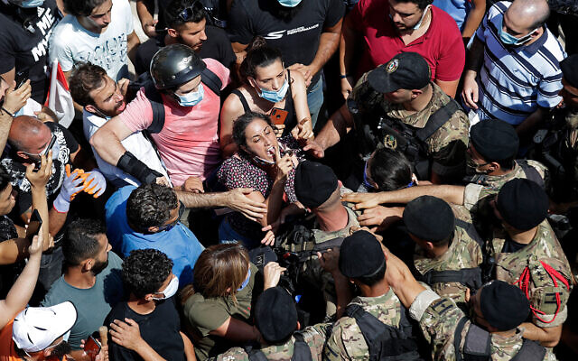 A woman yells at Lebanese soldiers during scuffles with soldiers as French President Emmanuel Macron a damaged area in Beirut, Lebanon, August 6, 2020. (AP Photo/Hassan Ammar)