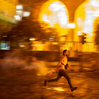 An anti-government protester throws back a tear gas canister at riot police, during a protest against the political elites who have ruled the country for decades, in Beirut, Lebanon, August 7, 2020. (AP Photo/Hassan Ammar)