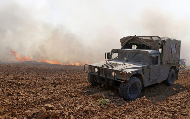 An IDF vehicle at the scene of a fire sparked by an incendiary balloon launched from the Gaza Strip, near Be'eri Kibbutz in southern Israel, on August 13, 2020. (Jack Guez/AFP)