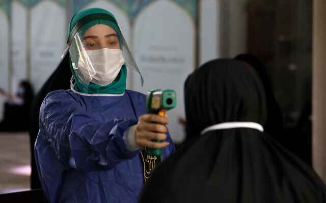 A volunteer wearing protective gear to help prevent the spread of the coronavirus checks temperature at a mosque in Tehran, July 30, 2020. (AP Photo/Vahid Salemi)