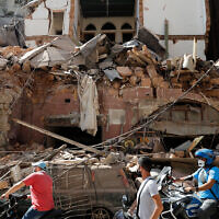 Citizens ride their scooters and motorcycles in front of a house that was destroyed in a massive explosion in the seaport of Beirut, Lebanon, August 5, 2020. (AP Photo/Hussein Malla)